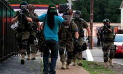 police dressed as soldiers, with automatic rifles, body armor and gas masks, aim their weapons at a black man
